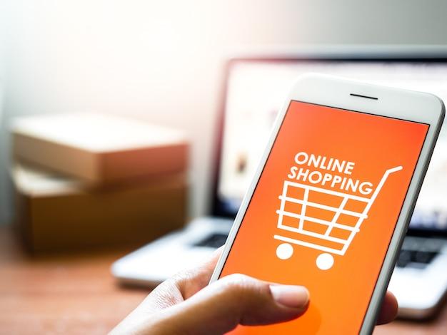 """Koncepcja zakupów online. słowa """"zakupy online"""" i ikona koszyka na pomarańczowym tle na ekranie smartfona."""