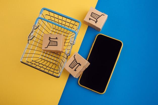 Koncepcja zakupów online. smartfon z mini pudełkami i koszykiem na niebiesko-żółtym tle