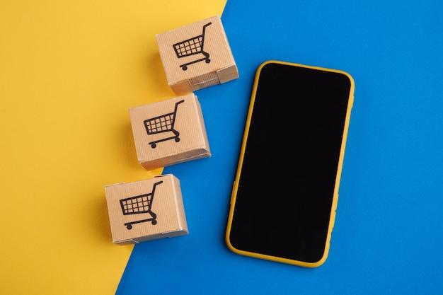 Koncepcja zakupów online. smartfon z mini pudełkami na niebiesko-żółtym tle