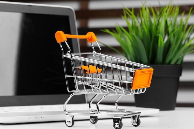Koncepcja zakupów online. wózek na zakupy, laptop na biurku