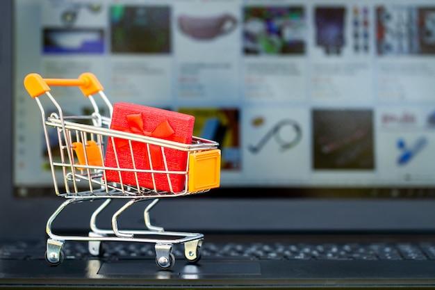 Koncepcja zakupów online. wózek na zakupy, małe pudełka, laptop na biurku