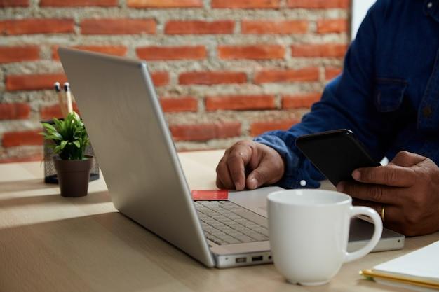 Koncepcja zakupów online, zbliżenie młodego człowieka za pomocą mobilnego smartfona i karty kredytowej dokonującej płatności online z laptopa na stole