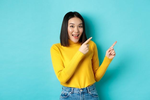 Koncepcja zakupów. piękna chinka w żółtym swetrze wskazująca palcami na baner z logo w prawym górnym rogu, uśmiechnięta rozbawiona, stojąca na niebieskim tle.