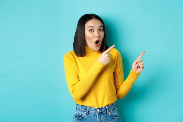 """Koncepcja zakupów. pod wrażeniem koreańskiej dziewczyny mówi """"wow"""" i wskazuje palcem w prawy górny róg, sprawdzając specjalną ofertę, stojąc nad niebieskim tłem."""