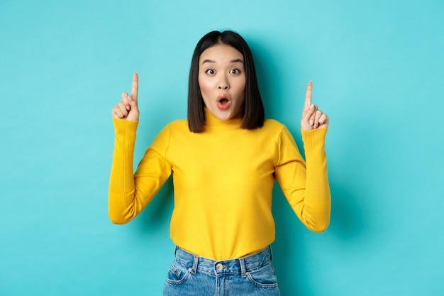 """Koncepcja zakupów. pod wrażeniem młoda koreańska kobieta pokazująca reklamę na górze, wskazująca palcami w górę i dysząca ze zdumieniem, mówiąca """"wow"""", stojąca na niebieskim tle"""