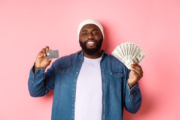 Koncepcja zakupów. przystojny młody czarny facet pokazując kartę kredytową banku i pieniędzy, uśmiechając się zadowolony, stojąc na różowym tle.