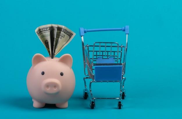 Koncepcja zakupów. skarbonka z bilardem i wózkiem mini supermarketu. niebieska ściana.