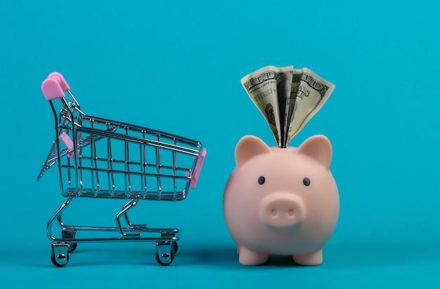 Koncepcja zakupów. skarbonka z wózkiem supermarketu dolar bil i miini. niebieska ściana.