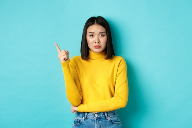 Koncepcja zakupów. smutna i ponura azjatka w żółtym swetrze wskazując palcem w lewo, marszcząc brwi i pokazując złe wieści na kopii przestrzeni, stojąc na niebieskim tle.