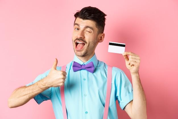 Koncepcja zakupów. świąteczny facet w muszce mrugający do kamery, pokazujący kciuki do góry z plastikową kartą kredytową, polecający dobrą ofertę sklepową, promujący bank, stojący na różowym tle.