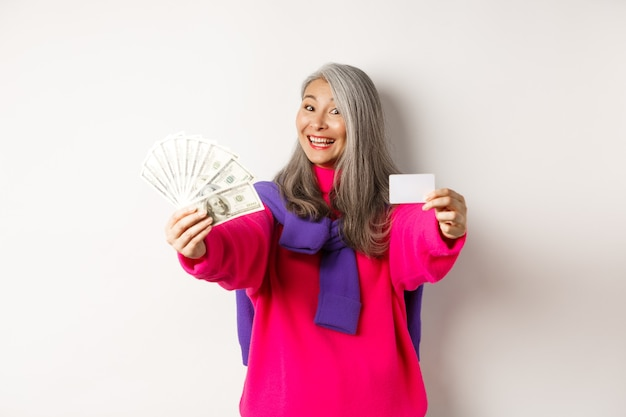 Koncepcja zakupów. wesoła azjatycka starsza kobieta pokazująca gotówkę i plastikową kartę kredytową, uśmiechająca się do kamery, stojąca na białym tle