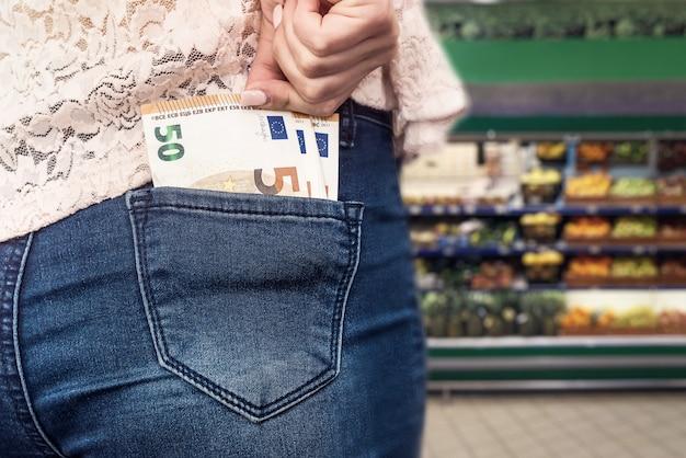 Koncepcja zakupów z banknotami euro w kieszeni dżinsów