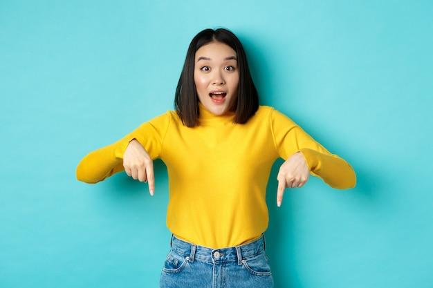 Koncepcja zakupów. zaskoczona atrakcyjna azjatycka dziewczyna pokazująca reklamę na niebieskim tle, wskazująca palcami w dół, gapiąca się w kamerę i mówiąca wow