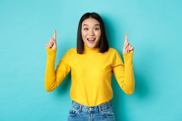 """Koncepcja zakupów. zaskoczona młoda koreanka pokazująca reklamę na górze, wskazująca palcami w górę i zdumiona dysząc, mówiąc """"wow"""", stojąc na niebiesko."""