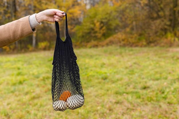 Koncepcja zakupów zero odpadów. bez plastiku. kobieca ręka trzyma czarną torbę eco string z pomarańczowymi i białymi dyniami na tle przyrody