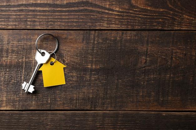 Koncepcja zakupu domu. klucze z breloczkiem dom na brązowym tle drewnianych. widok z góry. z miejscem na napis