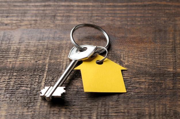 Koncepcja zakupu domu. klucze z dom pęku kluczy na zbliżenie brązowe drewniane tła.