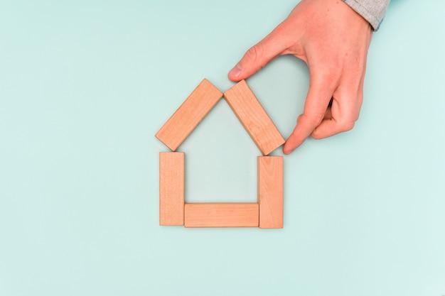 Koncepcja zakupu domu lub wynajmu. ręka trzyma drewniane klocki w formie domu