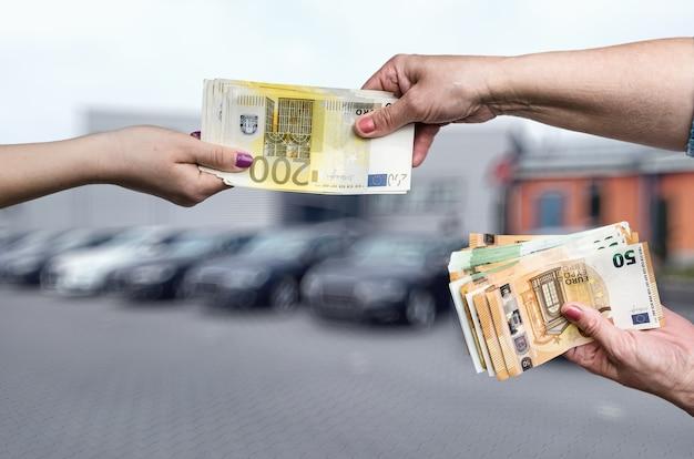Koncepcja zakupu samochodu, kobiece dłonie z banknotami euro