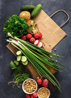Koncepcja zakupu żywności. torba papierowa ze składnikami do gotowania wegańskiego jedzenia. świezi warzywa, ziele, zboże i dokrętki na ciemnego tła odgórnym widoku ,.