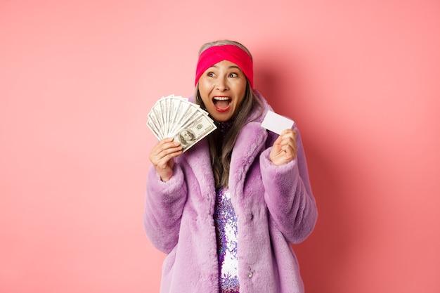 Koncepcja zakupy i moda. azjatycka starsza kobieta krzyczy szczęśliwa jak zwycięzca, trzymająca pieniądze w dolarach i plastikową kartę kredytową, wyglądająca na podekscytowaną, różowe tło
