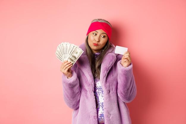 Koncepcja zakupy i moda. przemyślana azjatka trzyma dolary, ale myśli o płaceniu zbliżeniowym plastikową kartą kredytową