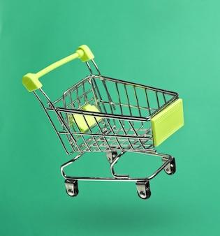Koncepcja zakupy minimalizmu. wózek na zakupy z zabawkami na niebieskim tle. zdjęcie z cieniem