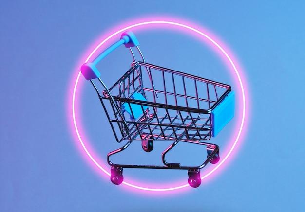 Koncepcja zakupy minimalizmu. wózek na zakupy z zabawkami, noc neonów. zdjęcie z cieniem