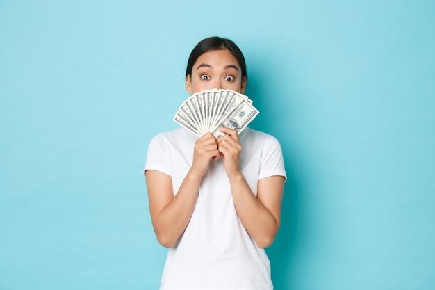 Koncepcja zakupy, pieniądze i finanse. podekscytowana i rozbawiona urocza azjatka przygotowała swoje dolary, aby zapłacić za koncert lub wspaniały produkt online, trzymając gotówkę na twarzy i wyglądając na zdumioną.