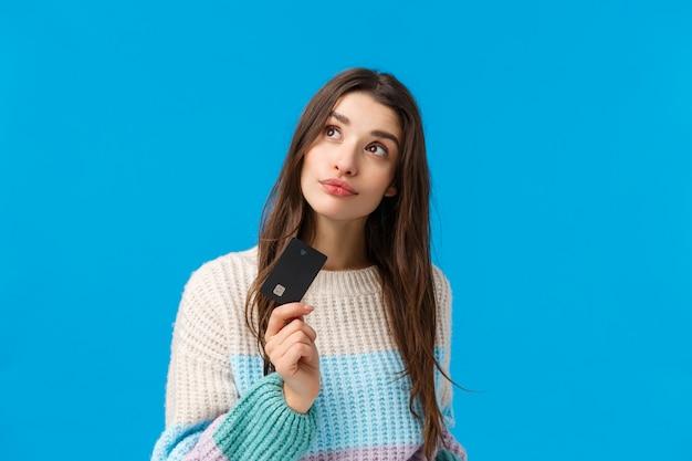 Koncepcja zakupy, rabaty i ferie zimowe. atrakcyjna marzycielska dziewczyna chce przygotować prezent na niespodziankę walentynkową, zastanawiając się, co kupić, zamówić online, trzymając kartę kredytową i starannie patrząc w górę