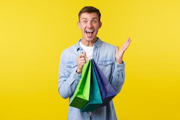 Koncepcja zakupy, rozrywka i rabaty. podekscytowany przystojny uśmiechnięty mężczyzna krzyczy ze szczęścia, gdy nosi torby ze sklepu z ofertami specjalnymi, reaguje zdumiony wspaniałymi cenami, żółtym tłem.