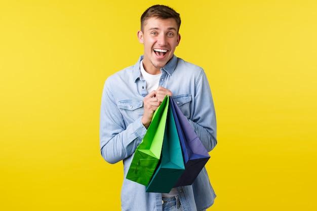 Koncepcja zakupy, rozrywka i rabaty. uśmiechnięty szczęśliwy przystojny facet zakupoholik, lubi kupować rzeczy na specjalnych ofertach, trzymając torby z zadowolonym wyrazem twarzy, żółte tło.