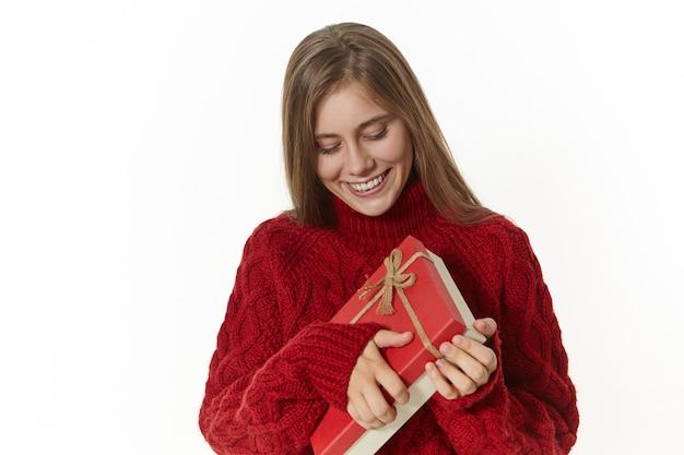 Koncepcja zakupy, wakacje, uroczystości i prezenty. urocza wesoła młoda europejka w ciepłym swetrze z długimi rękawami, uśmiechnięta podekscytowana, otwierająca czerwone pudełko z prezentem urodzinowym od przyjaciela