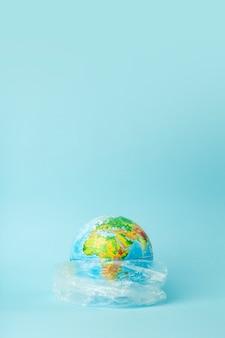 Koncepcja zanieczyszczenia plastikowej torbie. kula ziemska w plastikowej torbie na kolorowym tle. zanieczyszczenia oceanów tworzywami sztucznymi i odpadami, przyroda