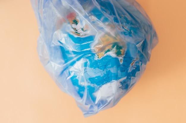 Koncepcja zanieczyszczenia ziemi. kula ziemska w ciasnej plastikowej torbie na pomarańczowo