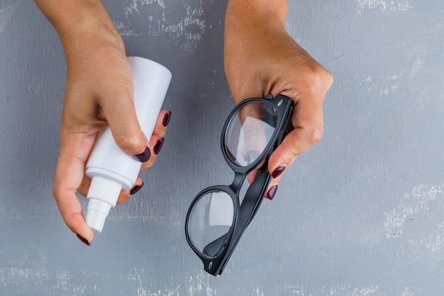 Koncepcja zapobiegania wirusom leżała płaska. kobieta czyszczenia okularów.