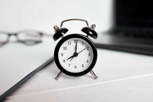 Koncepcja zarządzania czasem, miejsce pracy w biurze, notebook, komputer, laptop i czarny budzik na białym biurku drewnianym, miejsce na kopię