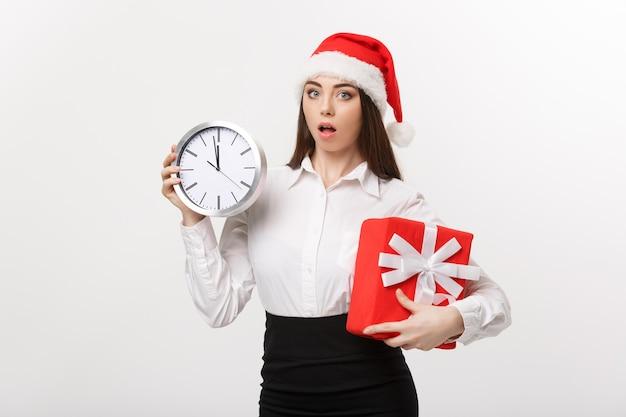 Koncepcja zarządzania czasem - młoda kobieta biznesu z santa hat trzyma zegar i teraźniejszość odizolowane nad białą ścianą.