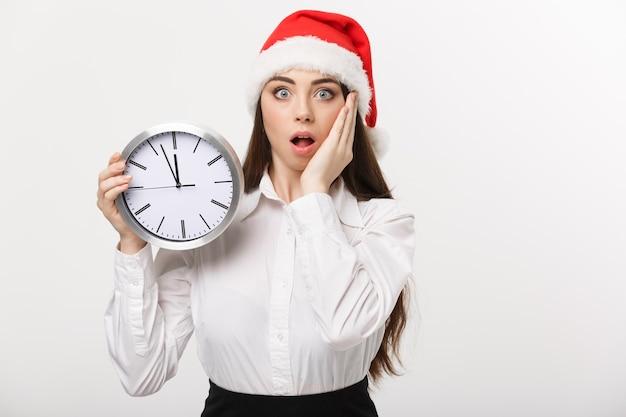 Koncepcja zarządzania czasem - młoda kobieta biznesu z santa hat trzyma zegar na białym tle nad białą ścianą.