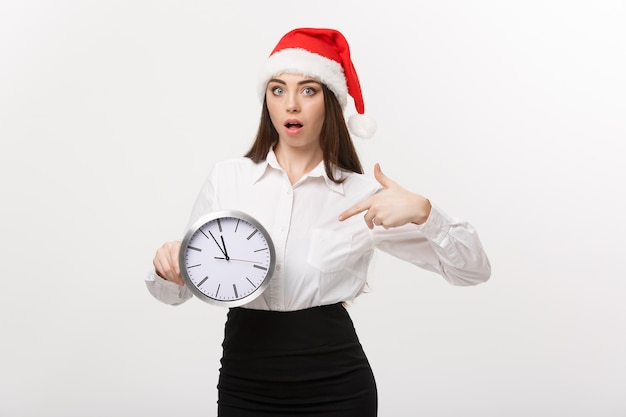 Koncepcja zarządzania czasem - młoda kobieta biznesu z santa hat trzymając i wskazując zegar na białym tle nad białą ścianą.