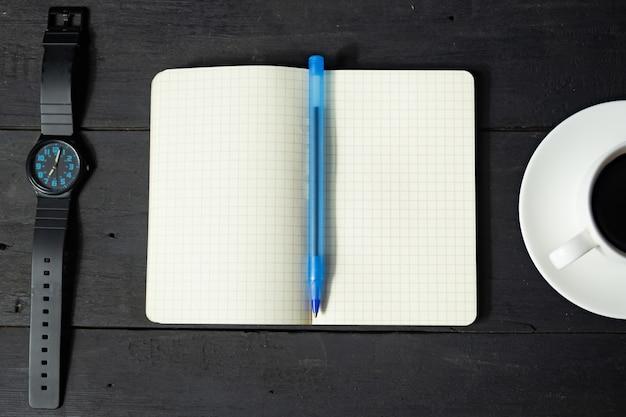 Koncepcja zarządzania czasem. notatnik, filiżanka kawy i zegarek mechaniczny, widok z góry