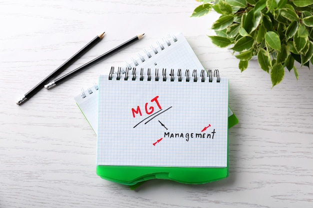 Koncepcja zarządzania. notatnik, ołówki i roślina doniczkowa na białym drewnianym stole