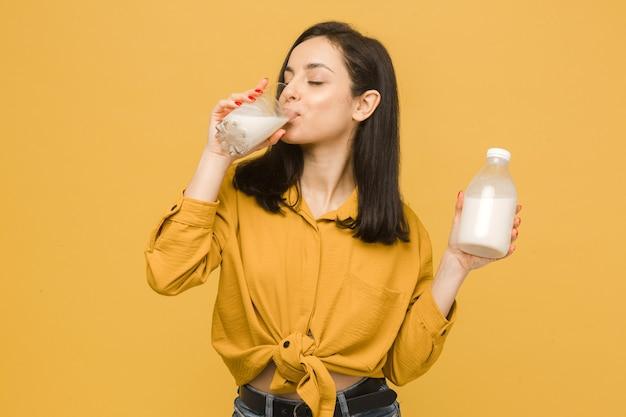 Koncepcja zdjęcie młodej kobiety pije mleko w szklance. nosi żółtą koszulę, na białym tle żółty kolor tła.
