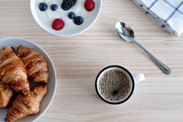 Koncepcja zdrowego breaskfast z czerwonymi owocami kawowego jogurtu i rogalika na drewnianym stole