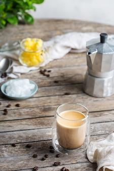 Koncepcja zdrowego, czystego jedzenia, keto, dieta ketogeniczna, poranny stół śniadaniowy. parzona kuloodporna kawa z organicznym olejem kokosowym, masłem ghee, ziarnami kawy. przytulna atmosfera kawiarni?