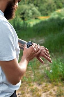Koncepcja zdrowego, inteligentnego stylu życia. muskularny sportowiec robi świetne ćwiczenia na zewnątrz w słonecznym parku. młody przystojny mężczyzna w odzieży sportowej sprawdzanie zegarka sportowego.