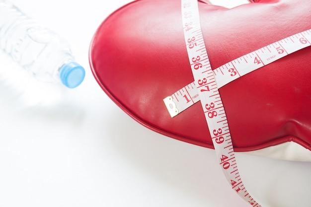 Koncepcja zdrowego odżywiania i pomiaru taśmy owiniętej wokół czerwonego serca na białym tle