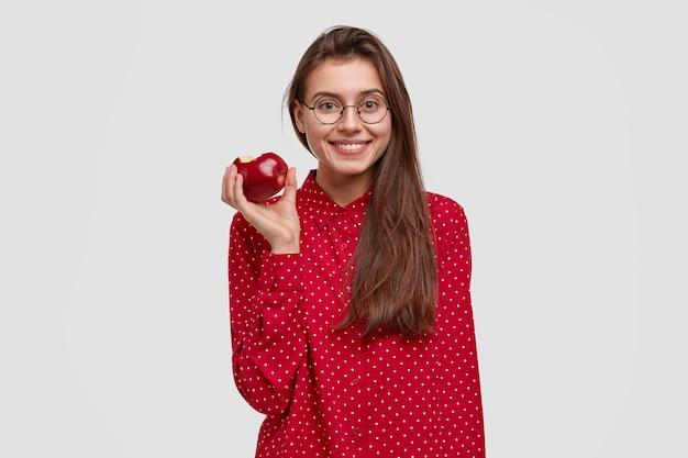 Koncepcja zdrowego odżywiania. ładna młoda dama je świeże czerwone jabłko, prowadzi zdrowy tryb życia, lubi surową wegetariańską żywność organiczną