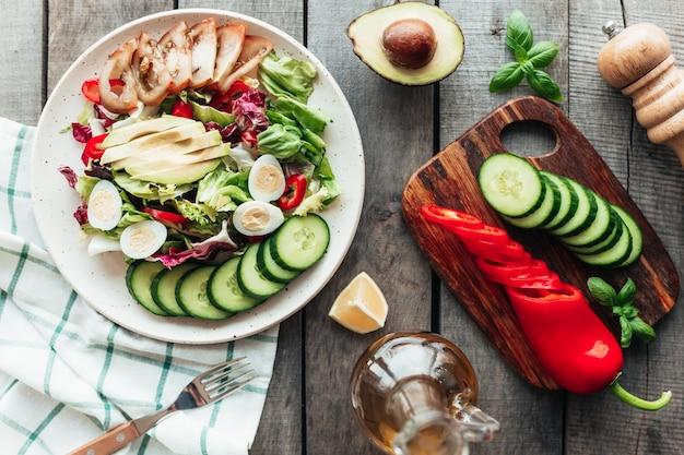 Koncepcja zdrowego odżywiania leżała płasko. dieta śródziemnomorska, talerz z liśćmi sałaty, jajko przepiórcze, awokado, pomidor, deska do krojenia z ogórkiem, papryka, bazylia, oliwa, cytryna na drewnianym stole