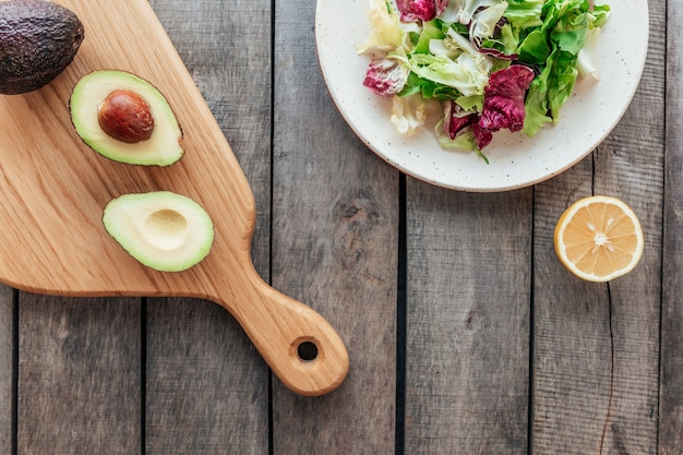 Koncepcja zdrowego odżywiania leżała płasko. dieta śródziemnomorska, talerz ze świeżymi liśćmi sałaty zielonej, liście radicchio fioletowe, deska do krojenia z połówkami awokado, jądro, cytryna na drewnianym stole